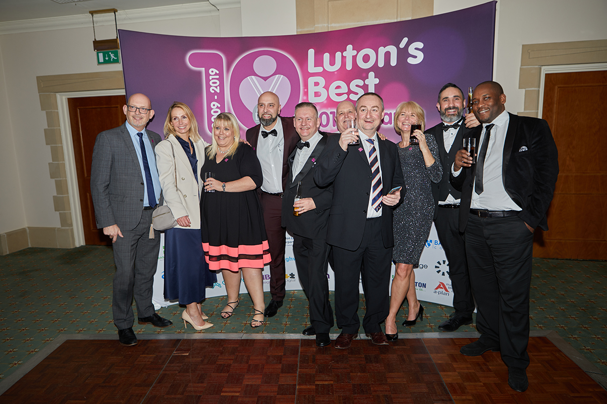 Group shot of people in front of a Lutons Best Backdrop